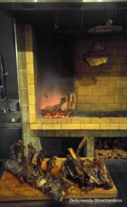 Meats cooking on open fire at Pasture Auckland