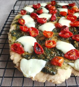 Close-up of Flatbread with cherry tomatoes, basil pesto, and mozzarella