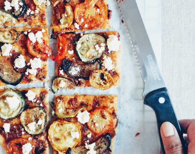 Flatbread with roasted vegetables and feta, sliced with hand holding a knife