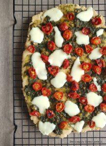 Flatbread with cherry tomatoes, basil pesto, and mozzarella