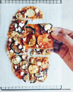 Flatbread with roasted vegetables and feta, sliced with hand holding up a slice