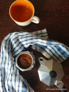 Moka pot with coffee and cup